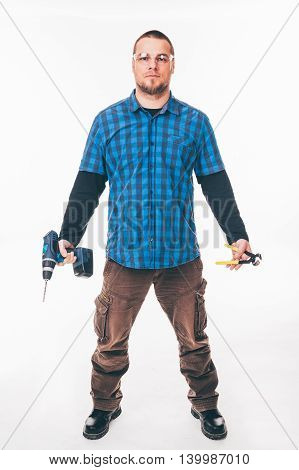 Pose of a standing man holding an electric drill and a pincer - isolated on white.
