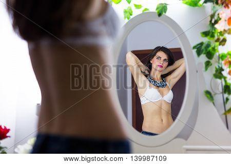 Sexy woman in front of the mirror putting on a nice necklace