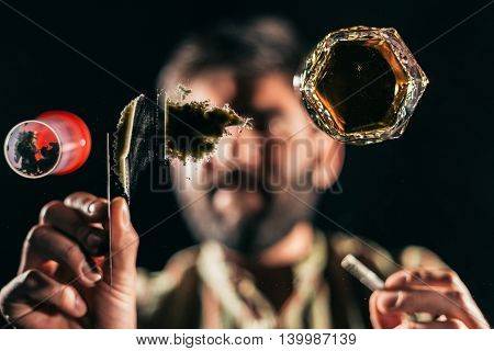 Man preparing a line of cocaine on a glass table