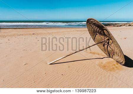 Fallen sun umbrella on the sand in a sunny windy day