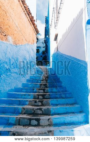 Stairs and walls painted in blue - small alleyway in Chefchaouen Morocco