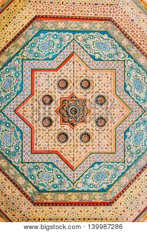 Marrakesh Morocco - February 8 2015: Floral pattern paintings on wood ceiling in Bahia Palace.