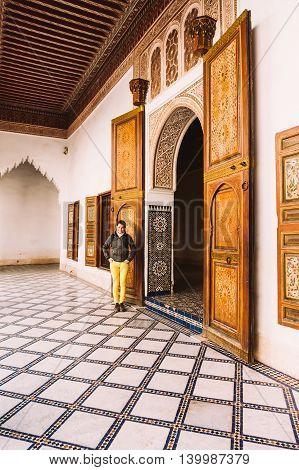 Marrakesh Morocco - February 8 2015: Smiling female tourist enjoying the interiors of the Bahia Palace.