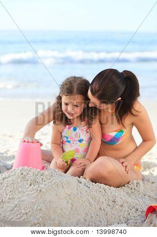 Tochter mit ihrer Mutter, die eine Sandburg