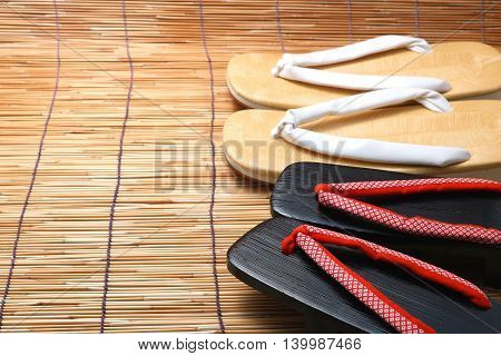 Japanese sandals for men and women on bamboo blinds. Concept of Japanese summer.