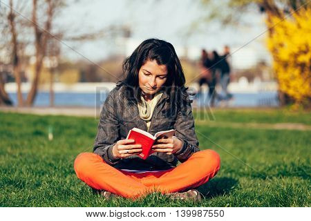 Closeup of a concentrated woman reading a book while sitting on the grass