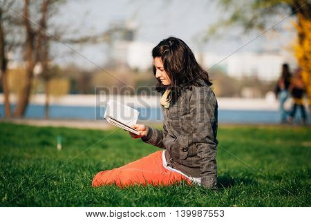 Profile of a woman reading a book and sitting on the tall grass