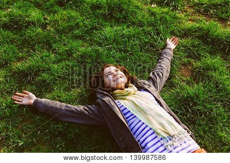 Happy smiling woman lying on grass in park with arms outstretched