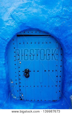 Unusual round wood door painted in blue - Chefchaouen Morocco