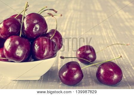 Cherries in white bowl on the wooden table. Filtered image.