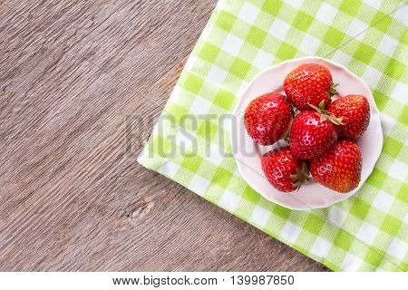 Fresh strawberries on green and white checkered napkin.Top view.