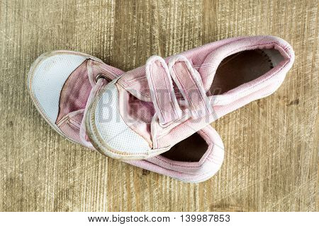 A pair of old pink sneakers on wooden surface.Top view.