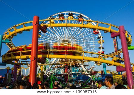 Los Angeles CA USA - July 6 2013: Speeding roller coaster in foreground and Ferris Wheel in background at Pacific Park near Santa Monica peer.