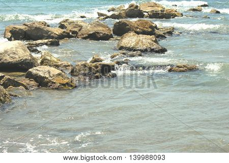 Large stones in a transparent sea water near the beach