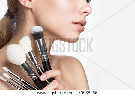 Beautiful young girl with a light natural make-up, brushes for cosmetics and French manicure. Beauty face. Picture taken in the studio on a white background.