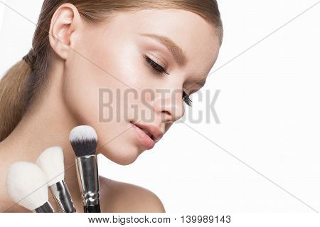 Beautiful young girl with a light natural make-up, brushes for cosmetics. Beauty face. Picture taken in the studio on a white background.