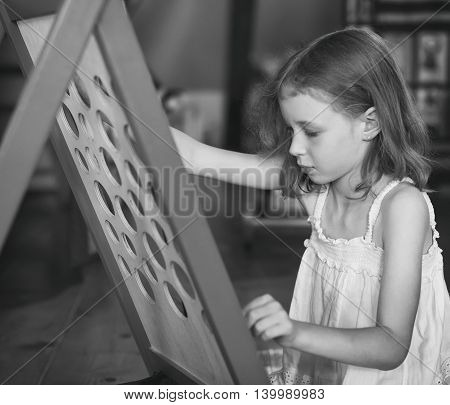Little girl is playing in educational game. Retro photo.