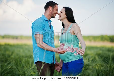 Happy Pregnant Couple On Wreath Field In Love