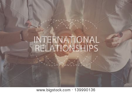 Globalizing world. Inspirational typographic quote about international relationships with cropped image of two men holding darts with a flag of USA in a background