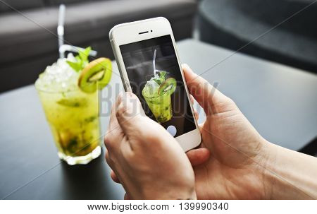 Young girl takes a  picture of fresh cocktail