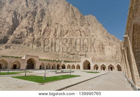 Historical hotel courtyard past mountain in Iran. Stone caravanserai structure