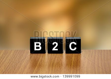 B2C or Business to consumer on black block with blurred background