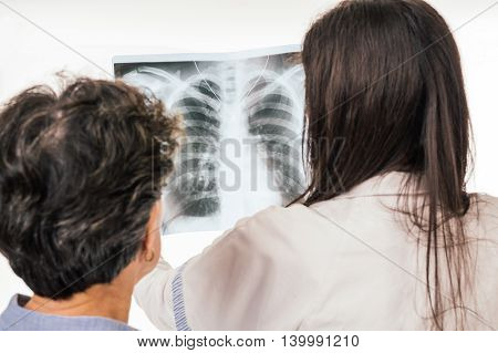 Senior patient standing close to doctor analyzing chest radiography - isolated on white