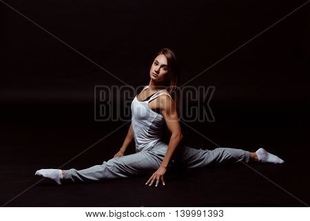 Muscular body of a young woman, abs close up. Amazing girl gymnast. Girl sitting on the splits.