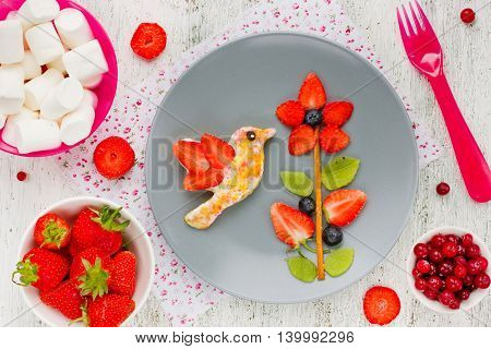 Toast with sugar and berry fruit in the form of a hummingbird on a flower. Fun food art idea for kids breakfast snack or dessert