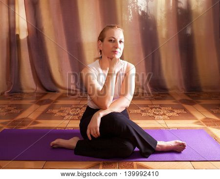 Portrait of a middle-aged woman who is sitting on the floor on a purple mat