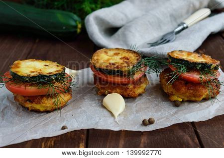 Snack in the form of a sandwich cutlet fried zucchini fresh tomatoes and greens