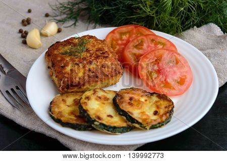 Fried cutlet tomato and zucchini on a white plate