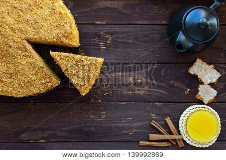Honey cake on a dark wooden background. Cutting a piece. The top view.