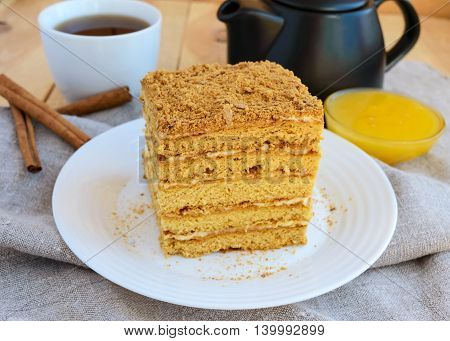 Honey cake and cup of tea on wooden background. Cutting a piece.