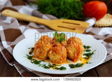 Meat balls on a white plate with greens.