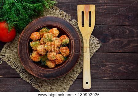 Meat balls with greens in a clay bowl. The top view