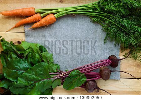 Young freshly picked beets and carrots on a wooden background. top view