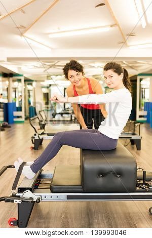 Woman exercising with the help of a female trainer