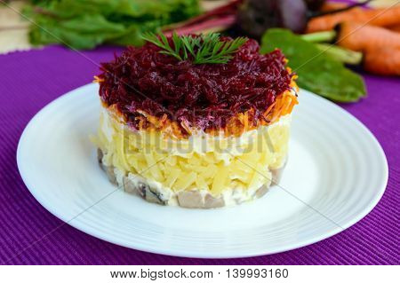 Salad with layers of cooked vegetables and salted fish (