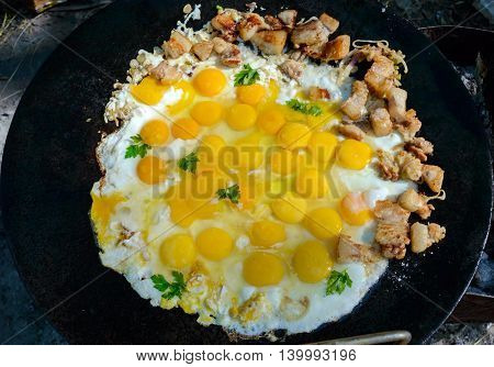 Fried eggs with pieces of pork on a large flat pan cooking outdoors.