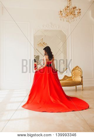 brunette stands back in a long red dress