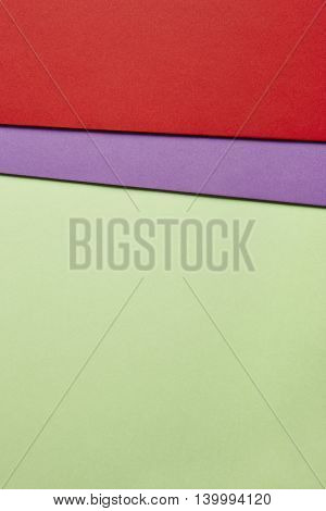 Colored cardboards background in green purple red tone. Copy space. Vertical