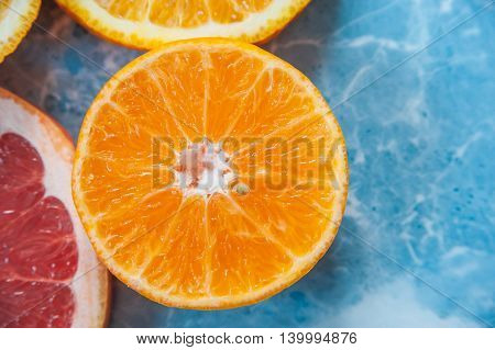 grapefruit orange and tangerine on blue background. Citrus texture