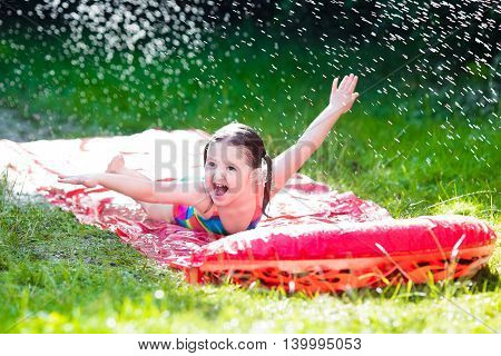 Little child playing with garden water slide. Kid jumping and splashing with gardening hose. Outdoor summer fun with backyard sprinkler for kids on hot sunny day.