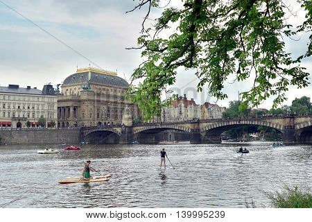 Prague Czech Republic - July 25 2016:Paddle surfing on the Vltava river in Prague in the background with the National Theatre