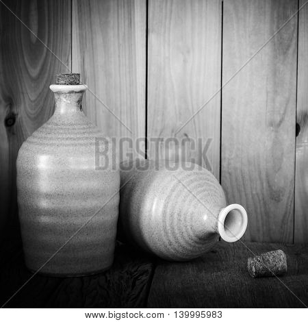 Still life of sake bottles with light on wood background in black and white filtered.