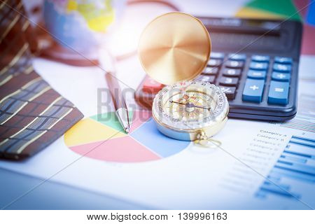Business analyzing investment charts with laptop calculator pen compass. Accounting. Vintage filtered.