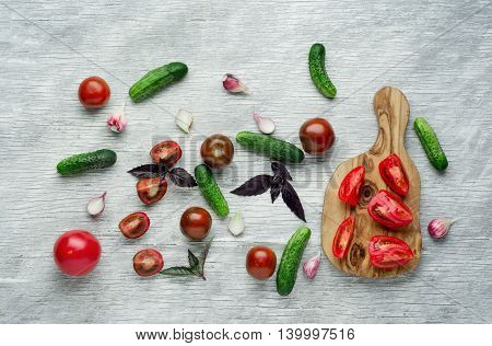 Tomatoes, herbs, onions and cucumbers over white wooden background.
