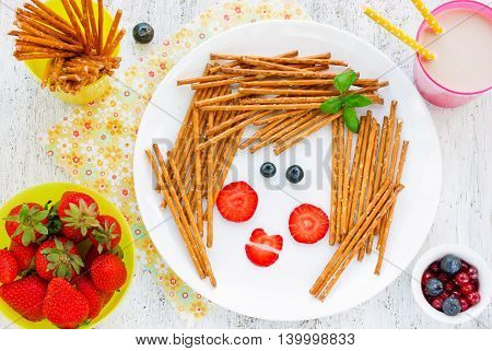Funny food art idea for healthy baby girl breakfast - cookies straws stickletti with berry in the form of glamor girl face. Picture on a plate fun with food concept