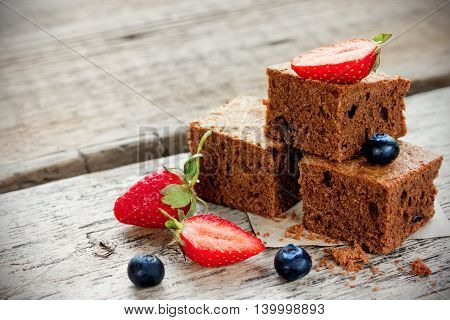 Brownie pieces with fresh berries on the old wooden background in rustic style selective focus
